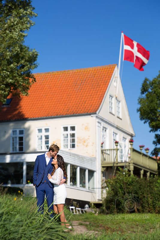 Beautiful and happy couple, nice background, blue sky and the wind is moving the flag in just the right way