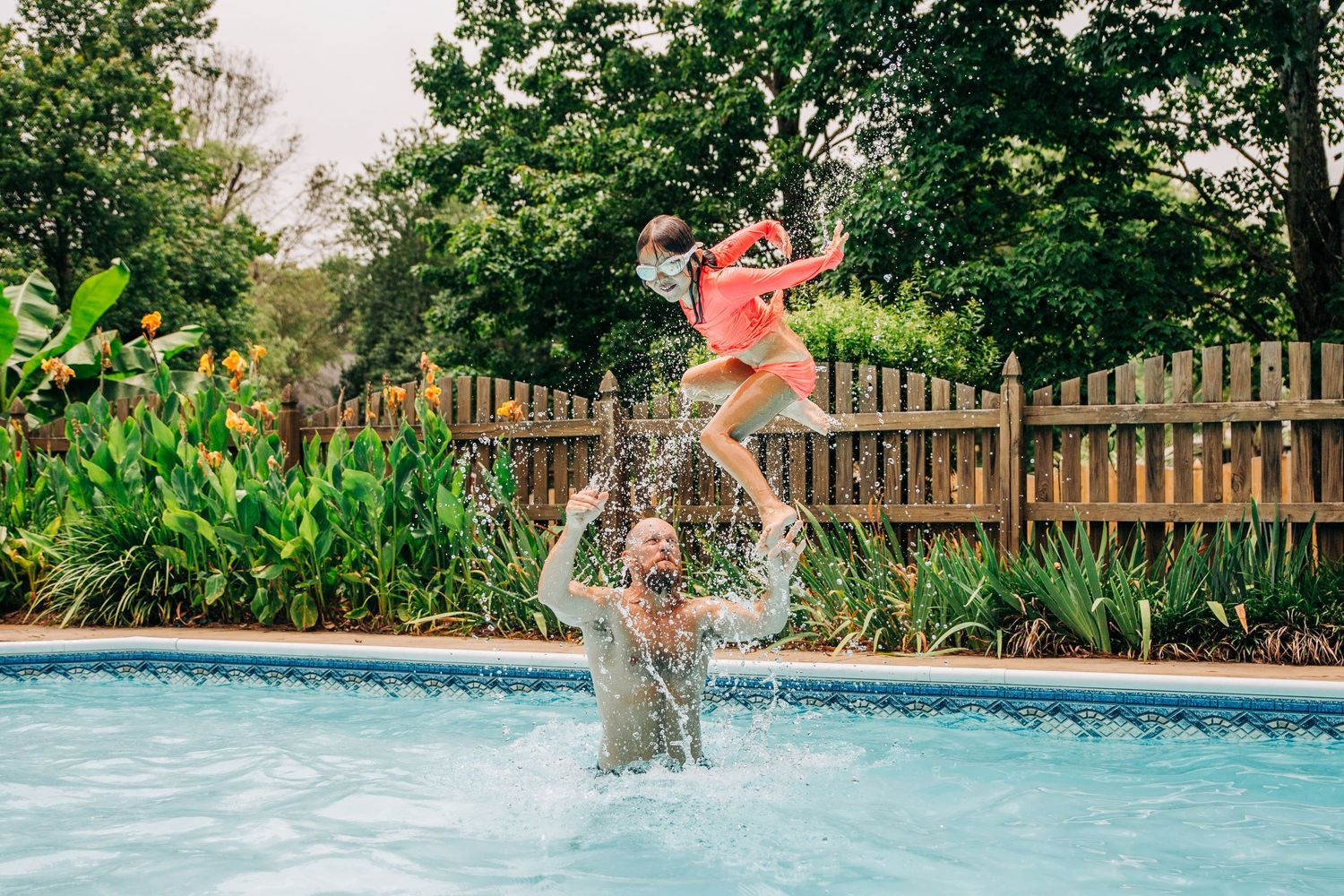 Dad throwing little girl in air in the pool