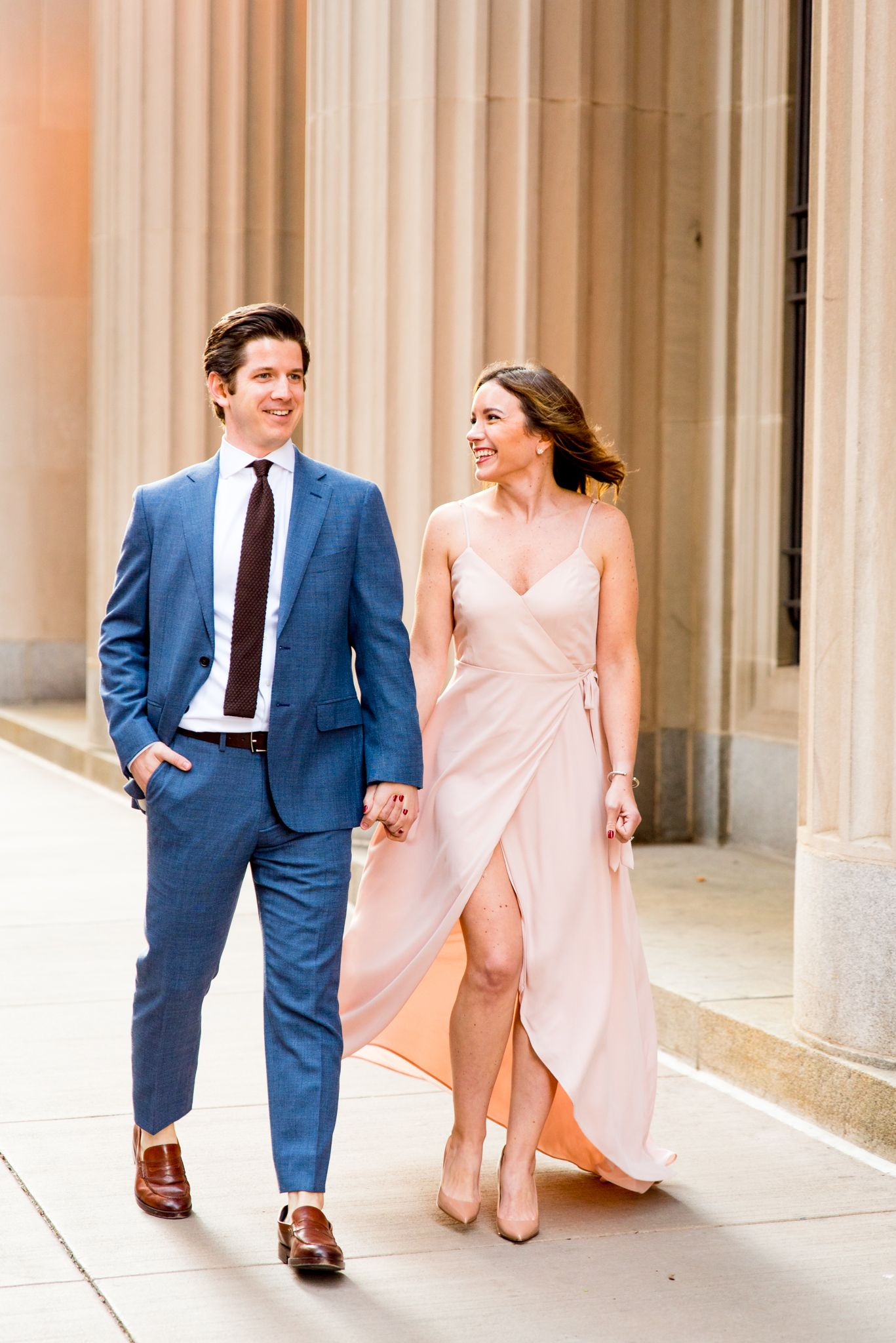 woman in blush pink dress holding hands with man in navy suit walking around Chicago Board of Trade