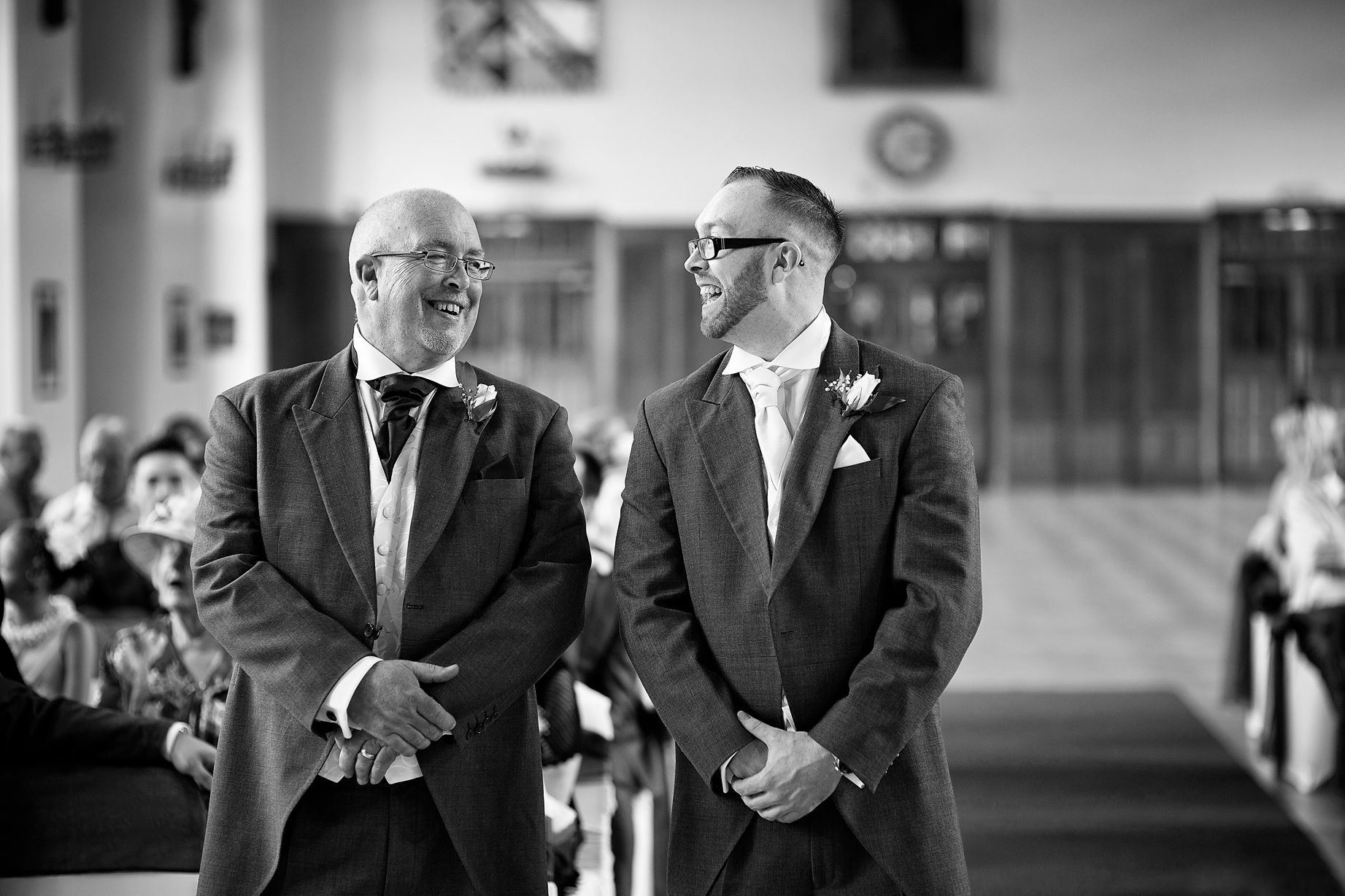 Bolton school wedding photographer image of groom and father of bride during the ceremony