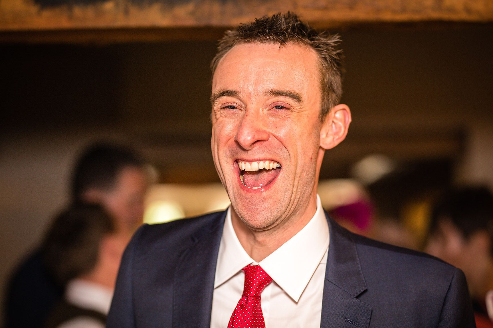 Male guest laughs during wedding breakfast snapped by Manchester wedding photographer