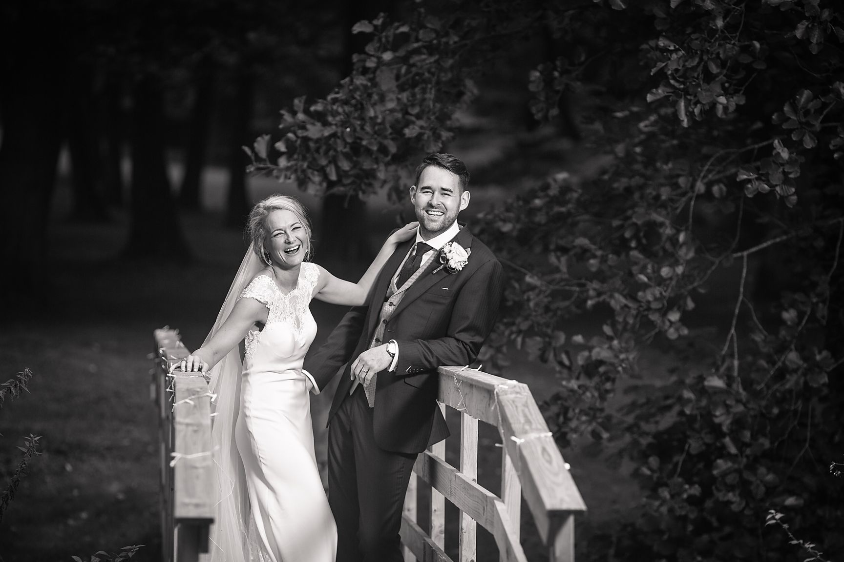Bride and groom stood on a bridge outside their Cheshire wedding marquee