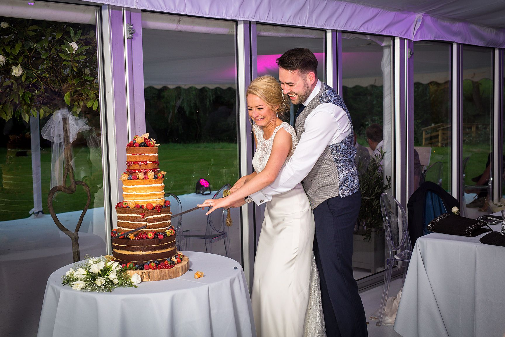 Bride and groom cut the cake at a Cheshire marquee wedding