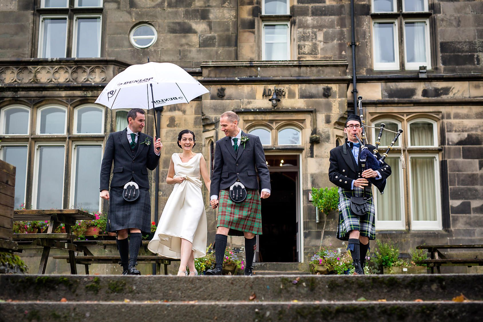 Bride and groom walk down stone steps at their Hargate hall wedding in the rain