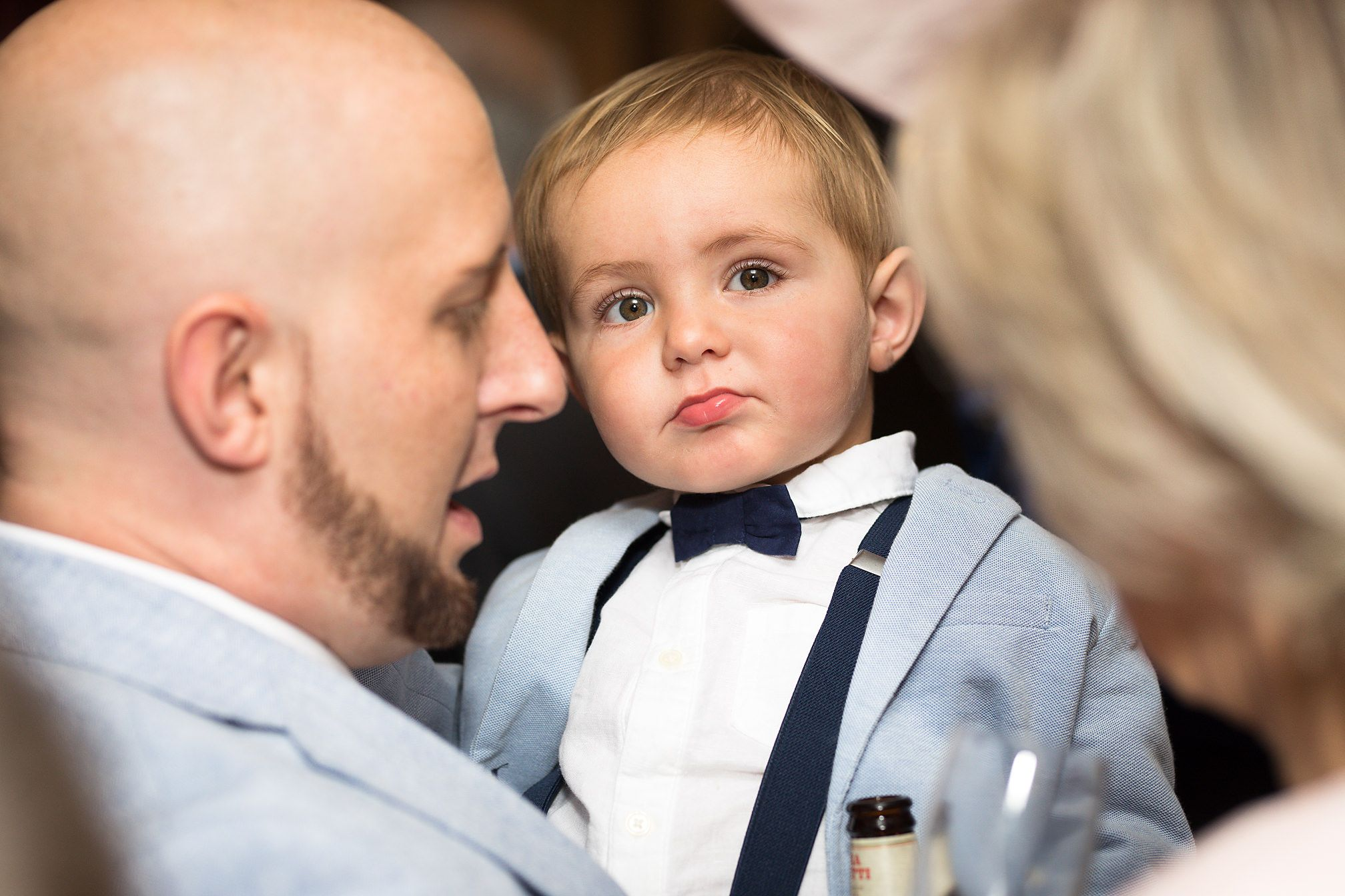 Little boy wedding guest is hugged and adored by his parents