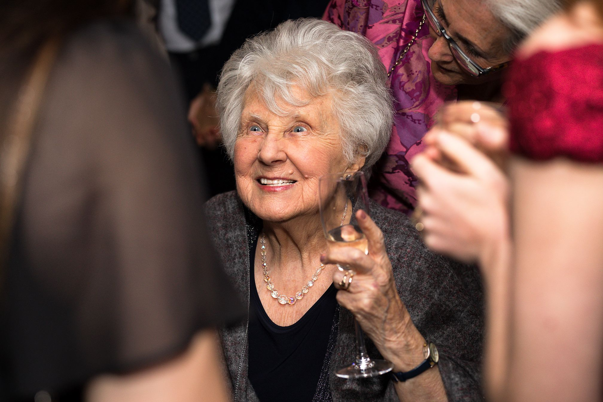 Grandmother of the bride smiles during indoor wedding celebrations amongst female guests
