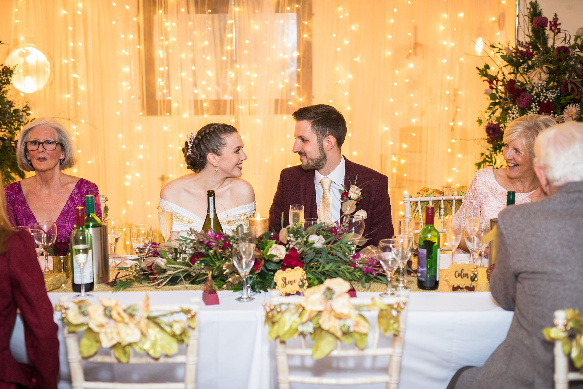 Bride and groom sat at their wedding table look adoringly into each others eyes surrounded by seated guests