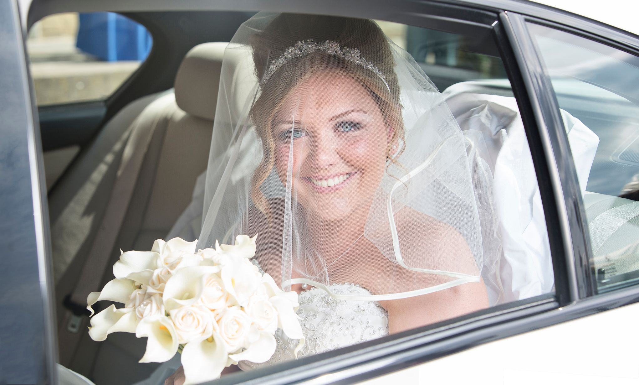 Bride arriving by car taken by Oldham wedding photographer