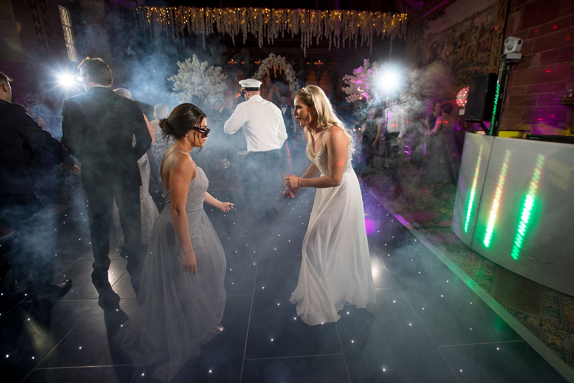 Peckforton castle wedding photography at evening party time with bride and bridesmaid dancing