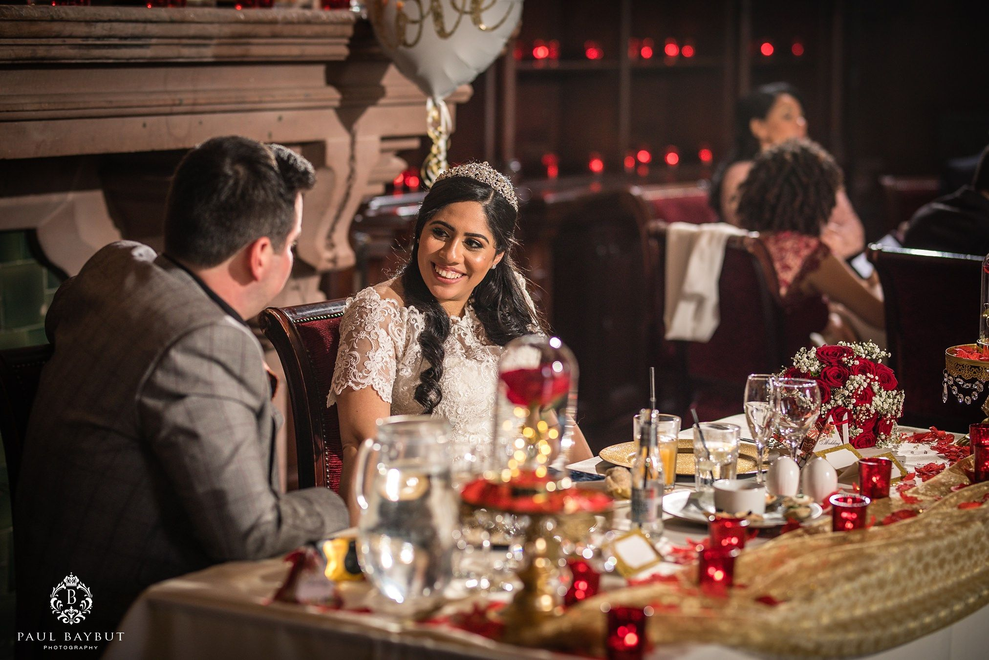 Smiling bride looks at her groom whilst seated at their wedding breakfast table in the great hall of Peckforton Castle