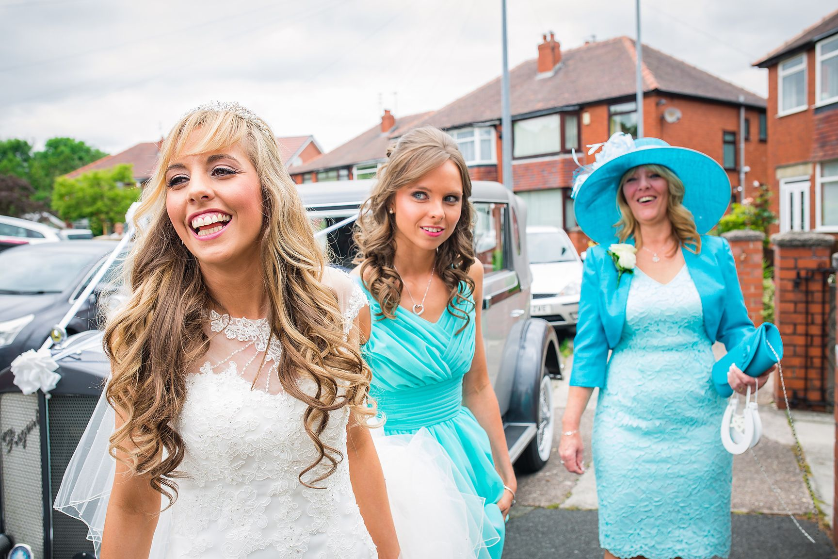 Smiling bride in white wedding dress is watched by her Mother and bridesmaid outside her house