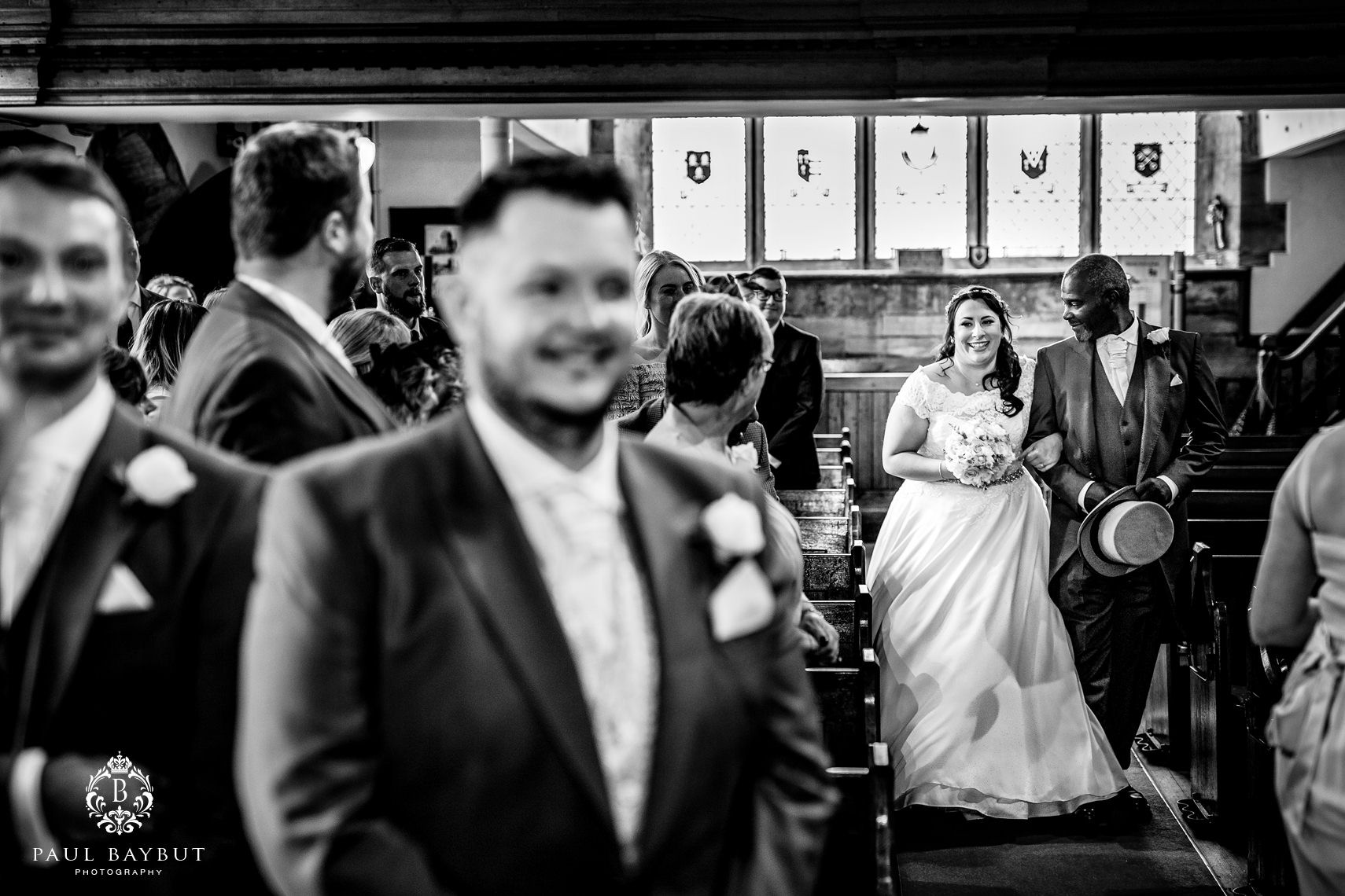 Nervous groom stands waiting in church as his bride walks down the aisle with her father on their Shrigley Hall wedding