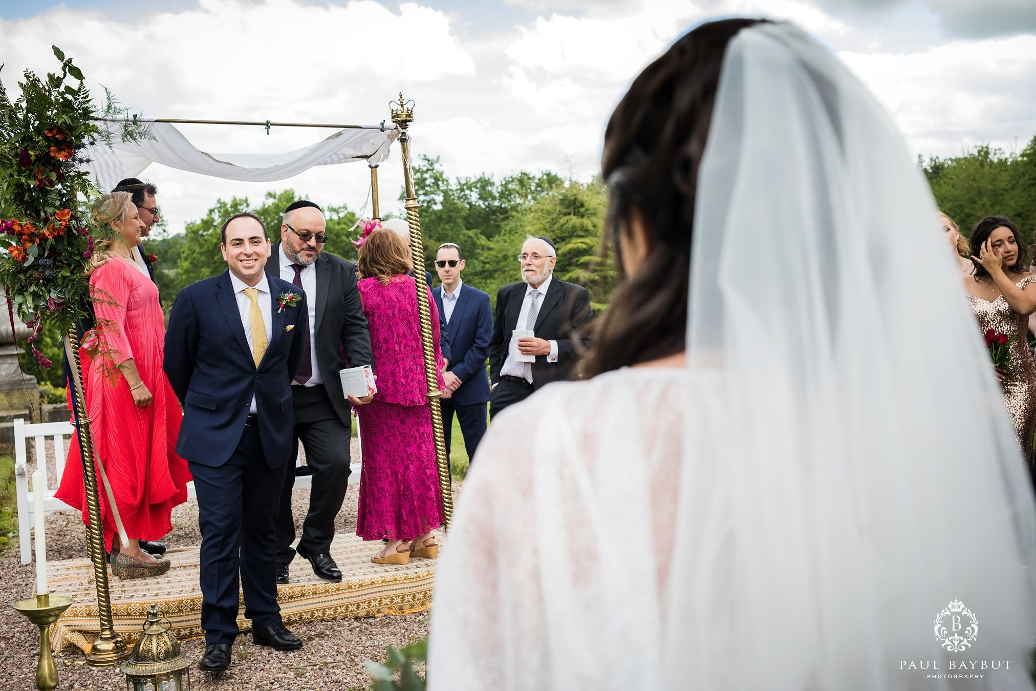 Jewish groom looks at his Persian bride in the gardens of their Tatton Park wedding