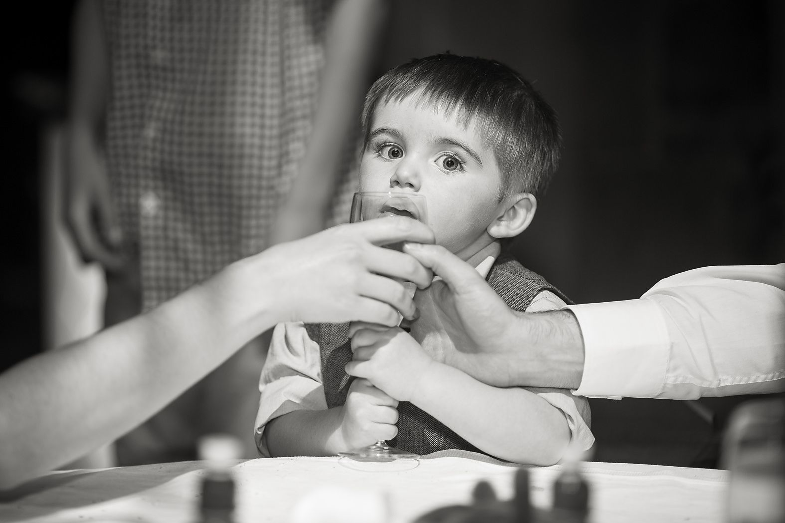 Parents try and take a glass of wine away from their small boy at the wedding table