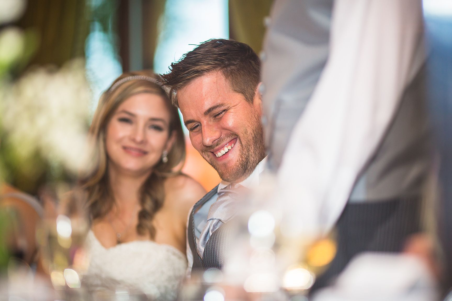 Bride and groom smile at best mans speech at the wedding breafast table