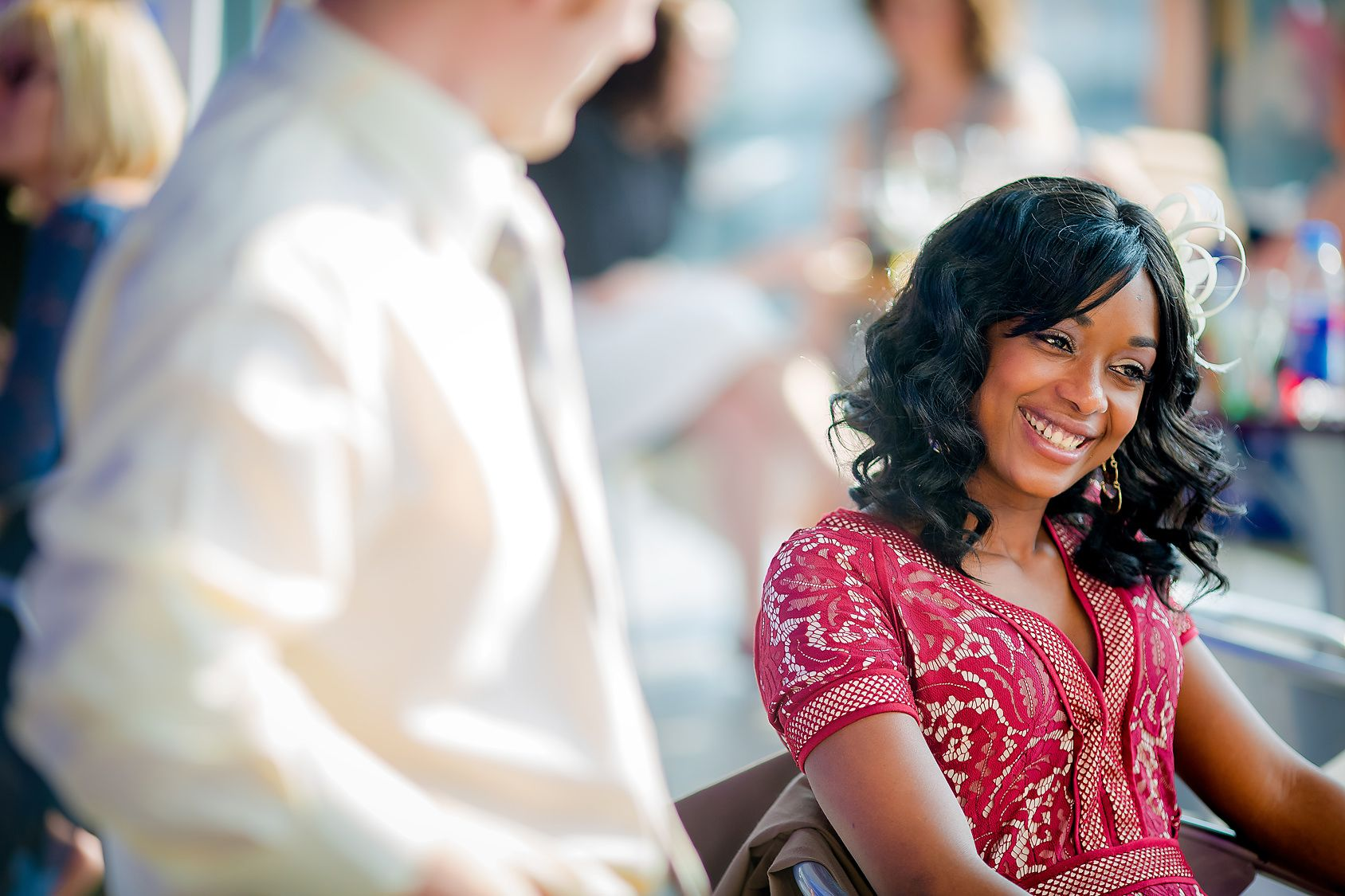 Beautiful black female smiles whilst a young man looks at her a wedding celebration at The Lowry Manchester