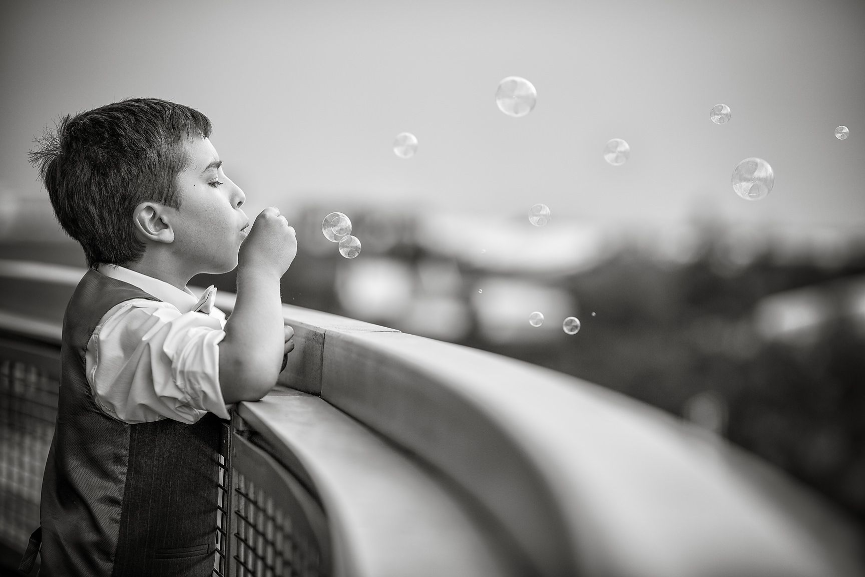 Young boy wearing a waistcoat blows bubbles over the balcony of The Lowry in Manchester