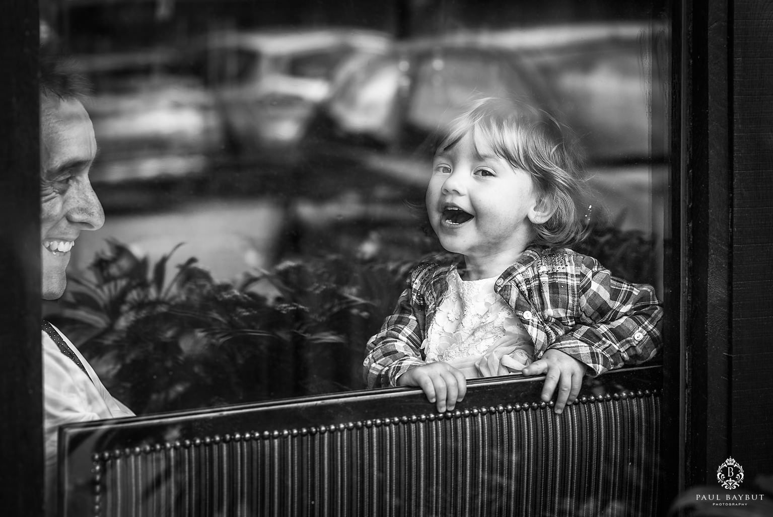 Little girl laughs heartily with her father behind a glass window