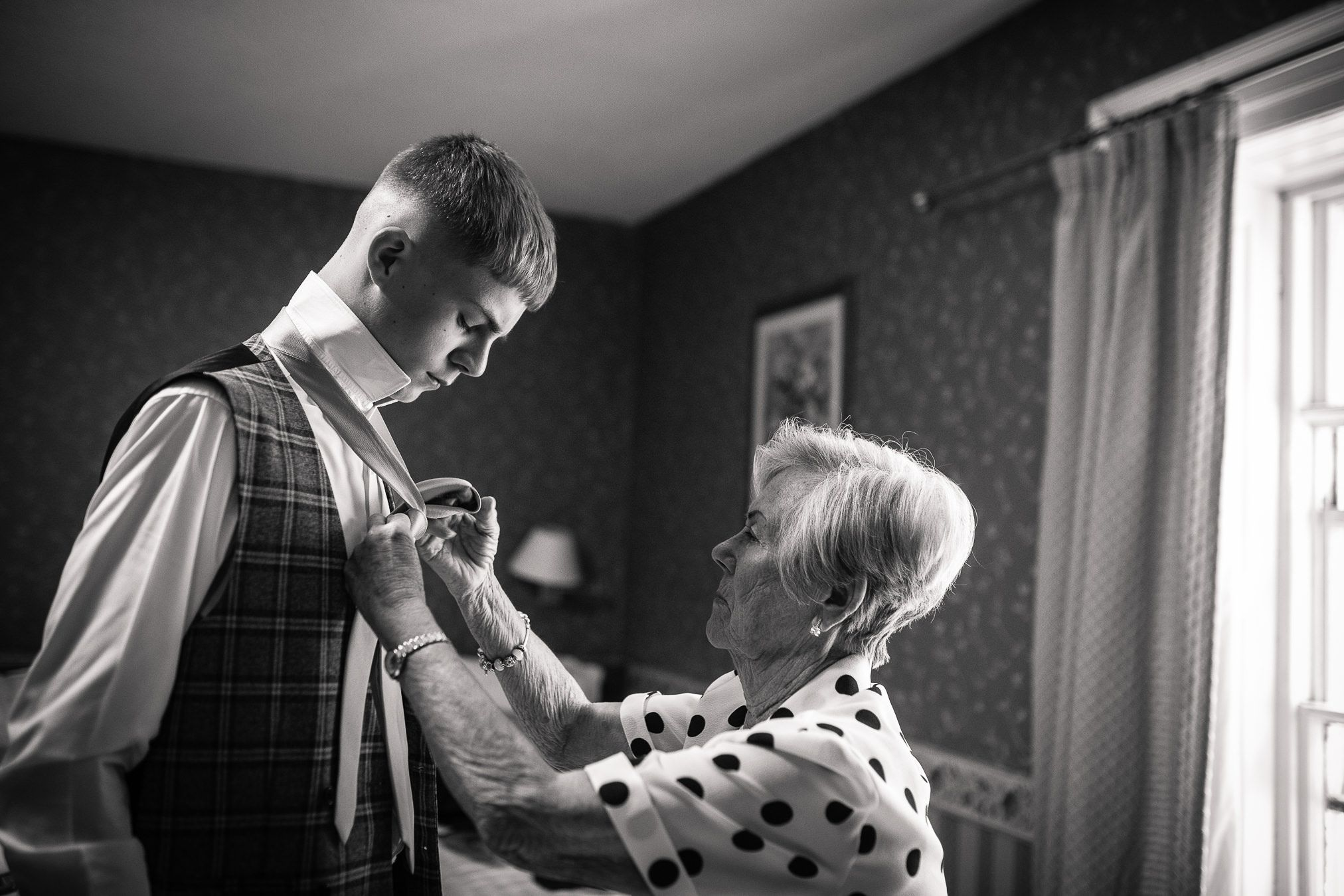 Grandmother helps a groomsman with his tie at a Wortley Hall wedding