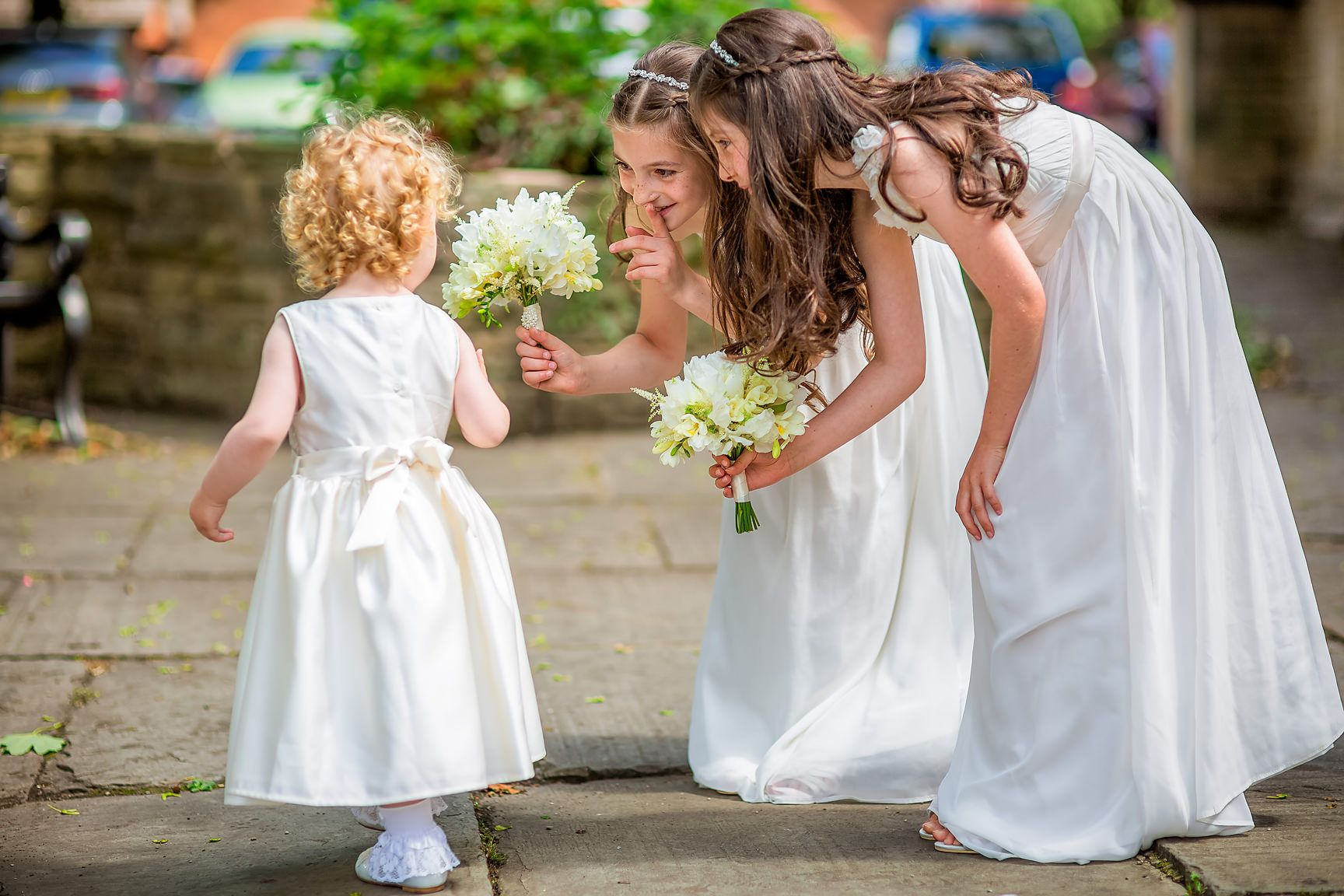 Tiny toddler bridesmaid is greeted by two young bridesmaids all dressed in white outside church