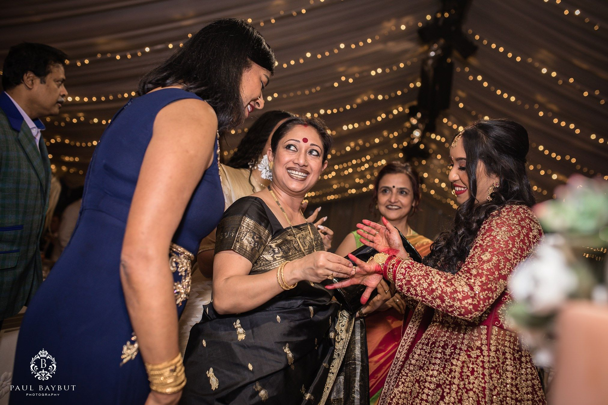 Indian wedding guests look at the brides ring inside the marquee at Thornton Manor