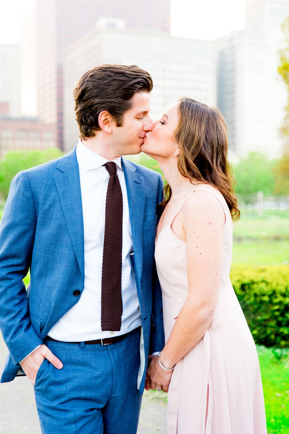 man in navy suit kissing woman in light pink dress in Grant Park for Chicago sunset engagement pictures