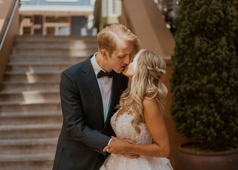 Bride and Groom share a kiss at the base of steps