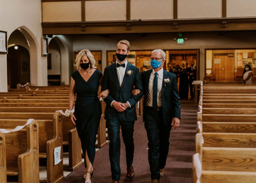 Groom and his parent's walk down the aisle