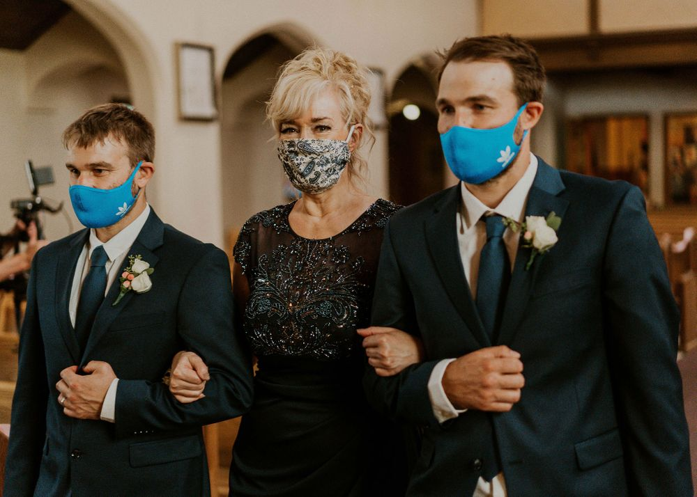 Mother of the bride being escorted down the aisle in masks