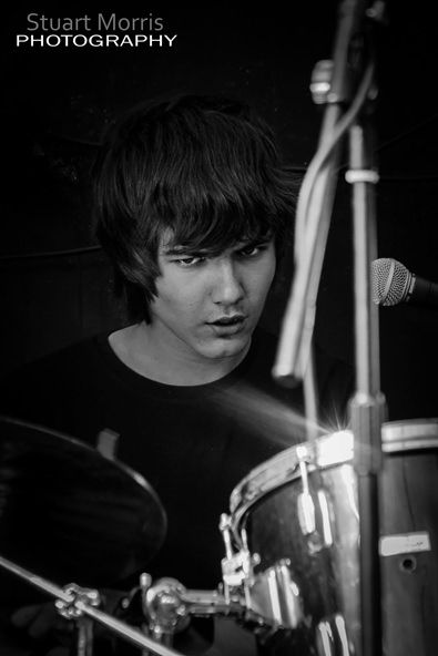 close up of stilia drummer looking serious playing on stage in concert