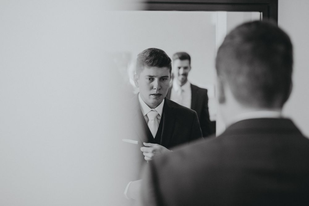 black and white photo of groom adjusting his tie in the mirror
