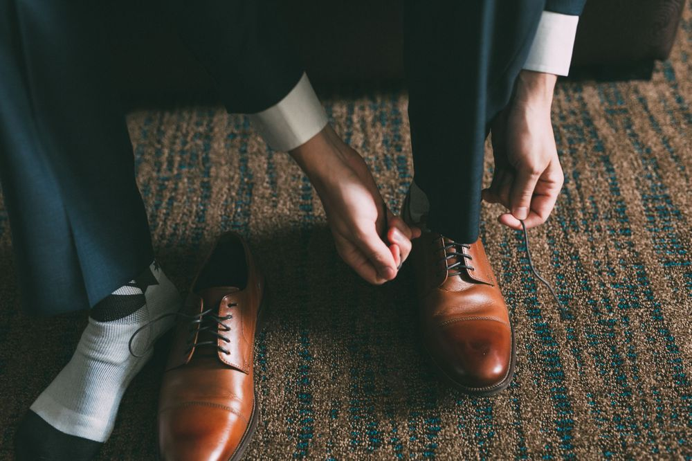 groom tying dress shoes while getting ready on his wedding day