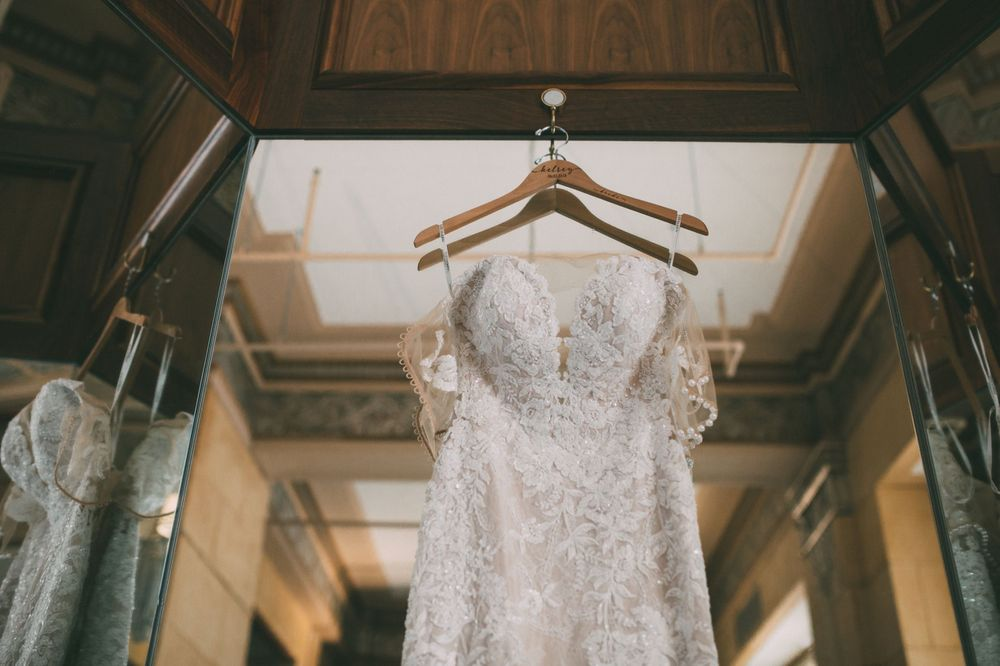 wedding dress hanging in front of mirror