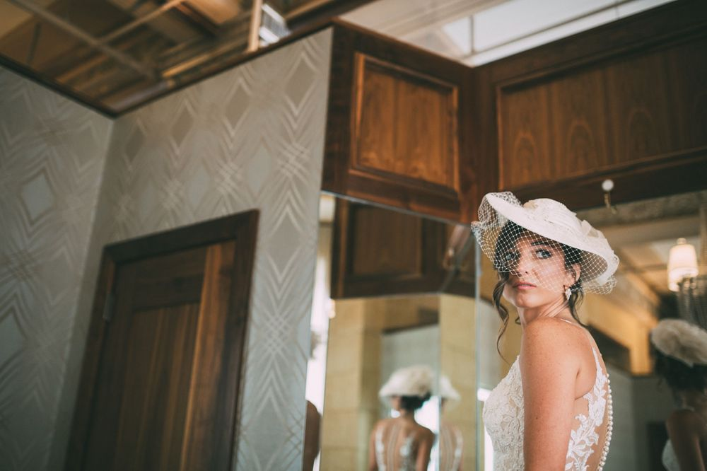 bride in her wedding dress looking over her shoulder in front of a mirror