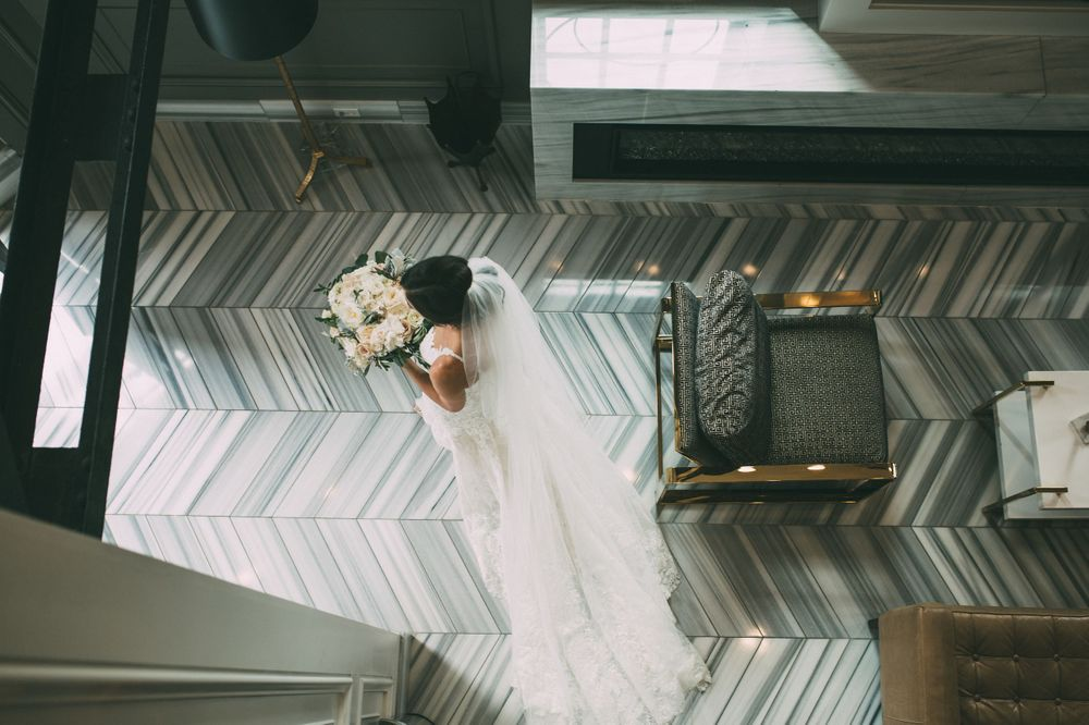 photograph from above as bride walking through room on marble floor