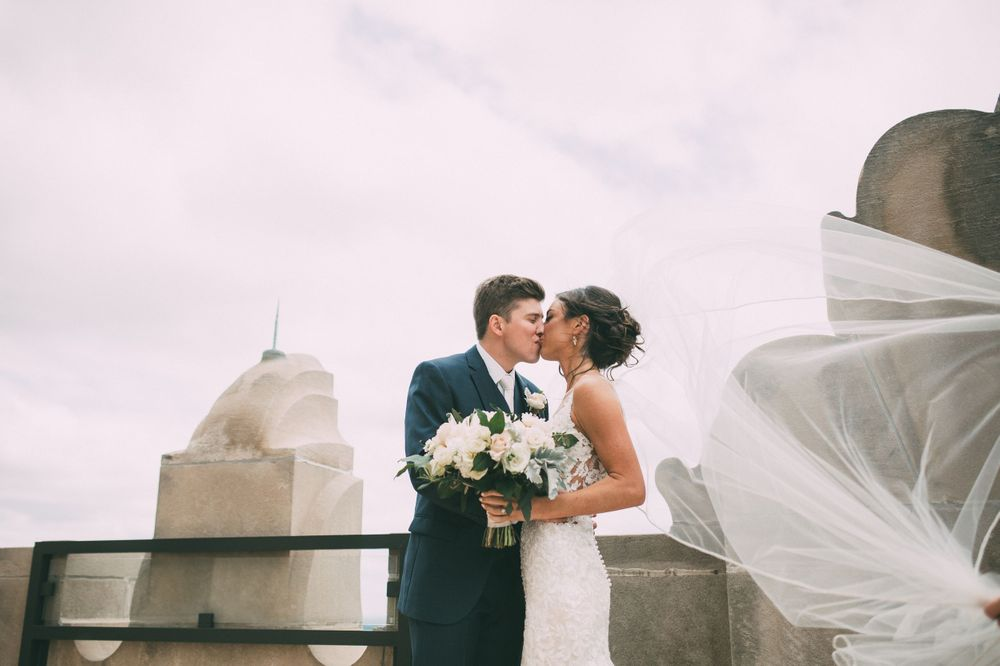 bride and groom kiss on top of Power and light building in kansas city