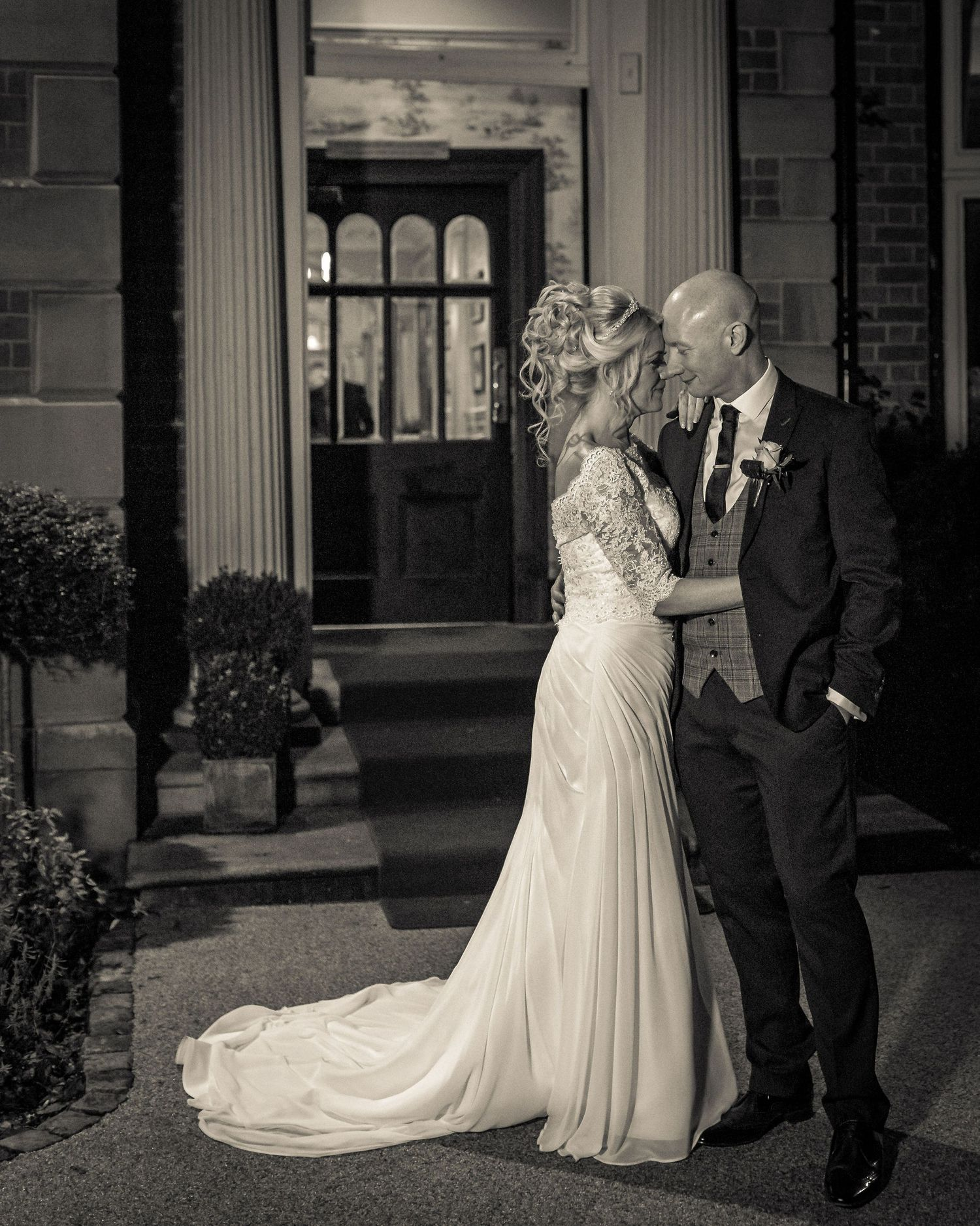 night time portrait of the bride and groom standing very close together smiling in the doorway to ashfield house