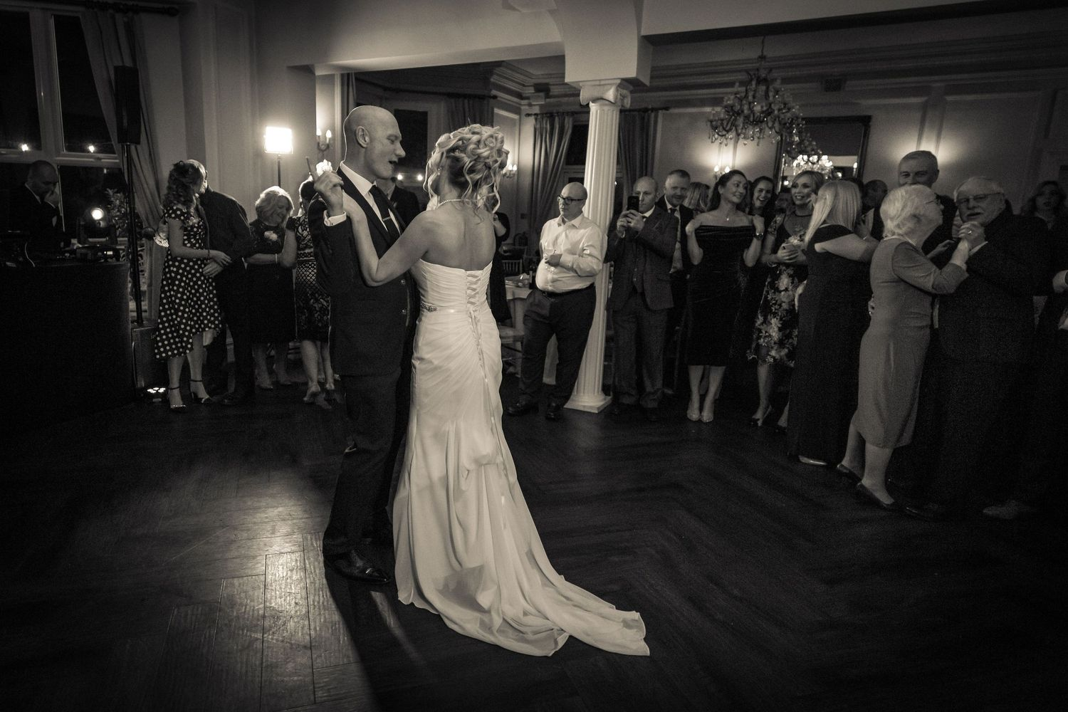 black and white shot of the bride and groom during their first dance watched by their guests