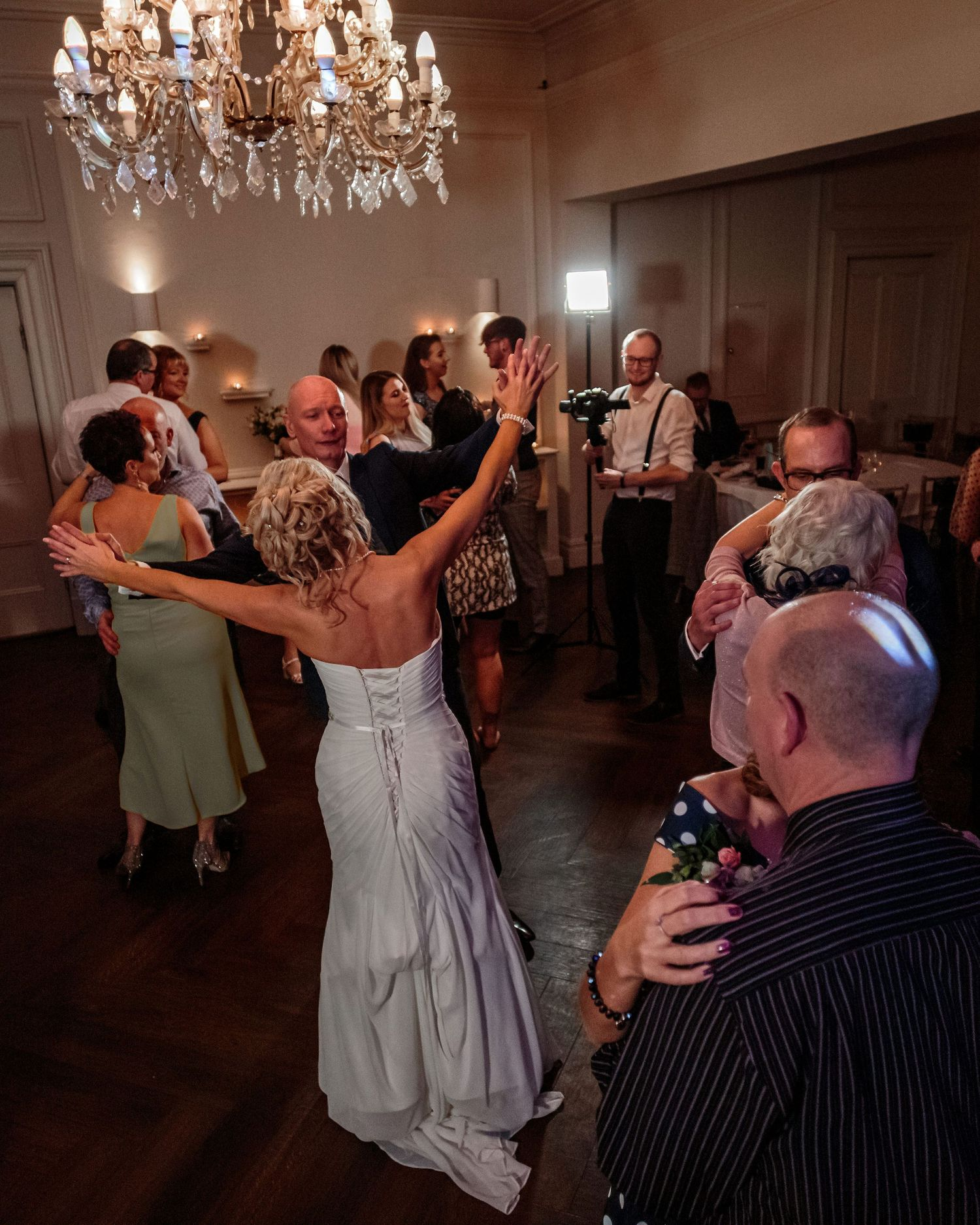 bride and groom with their arms in the air as they newlyweds are joined on the dance floor by their wedding guests