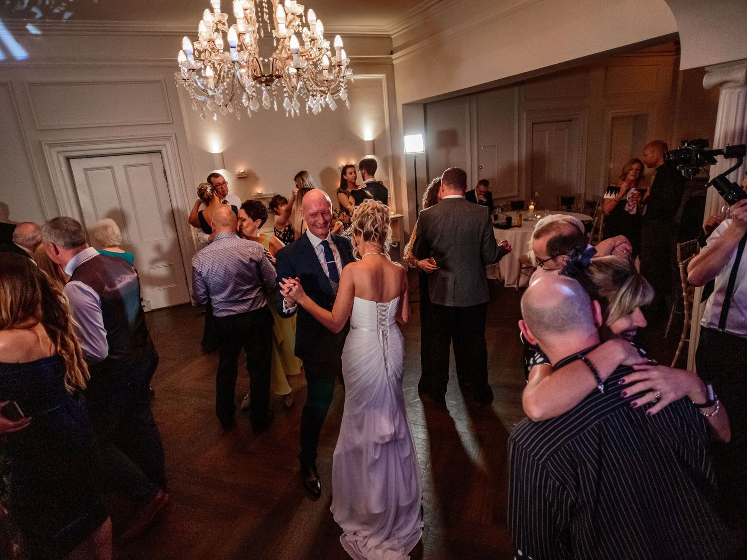 bride and groom are joined by their guests on the dance floor during their first dance