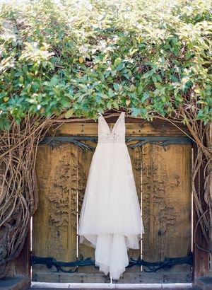 Brides dress hanging in front of vintage door at Kennolyn wedding