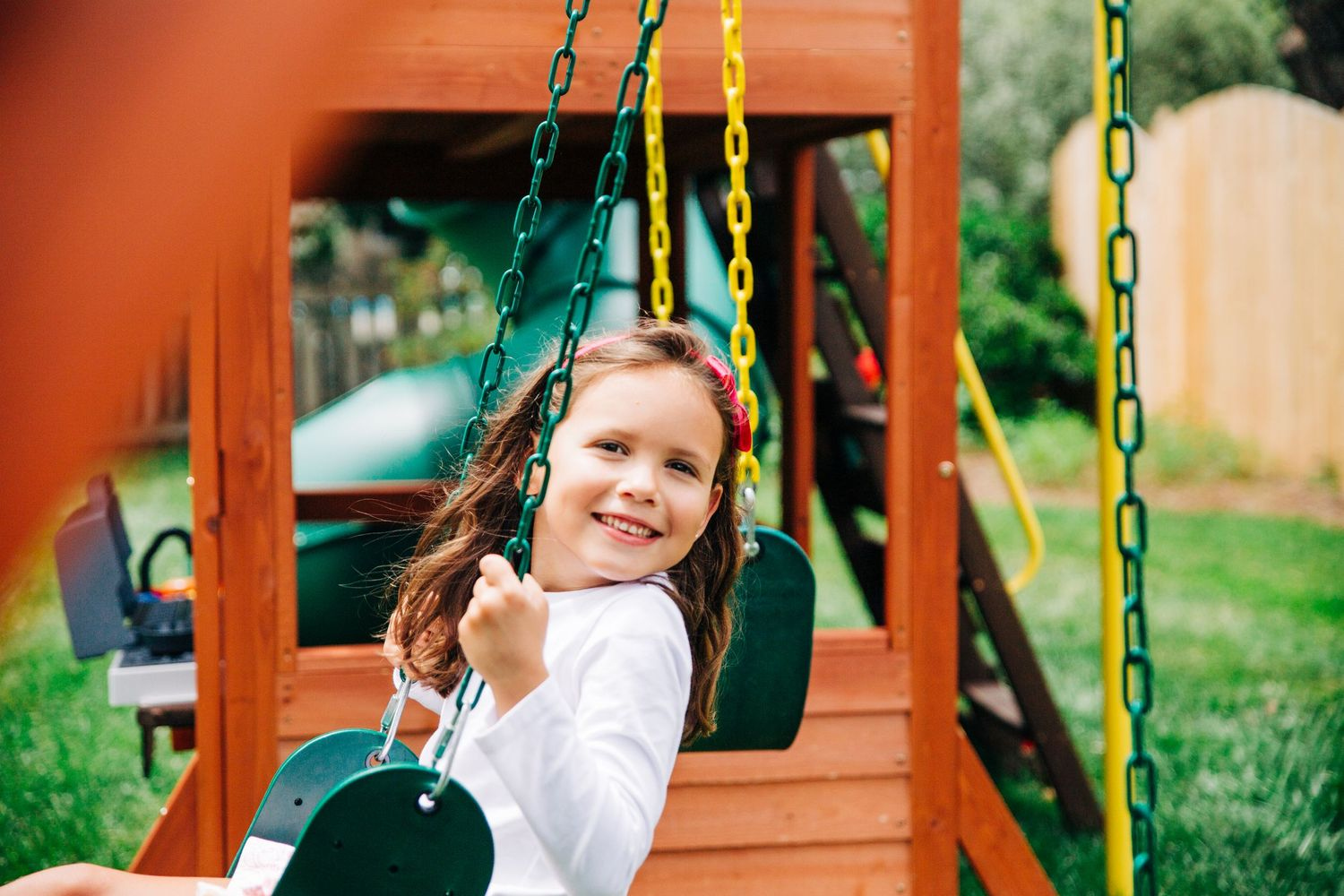 Young girl sitting on swing set during documentary family photography session in Charlotte, NC