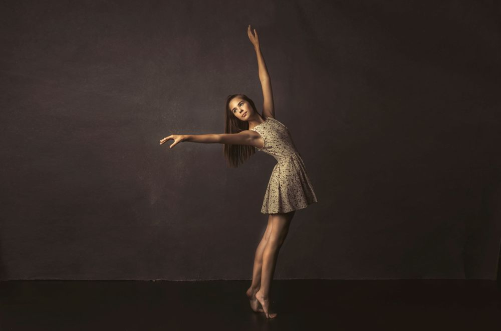 Beautiful girl stands gracefully in short dress in YEG studio photograph by Ammara Crittenden
