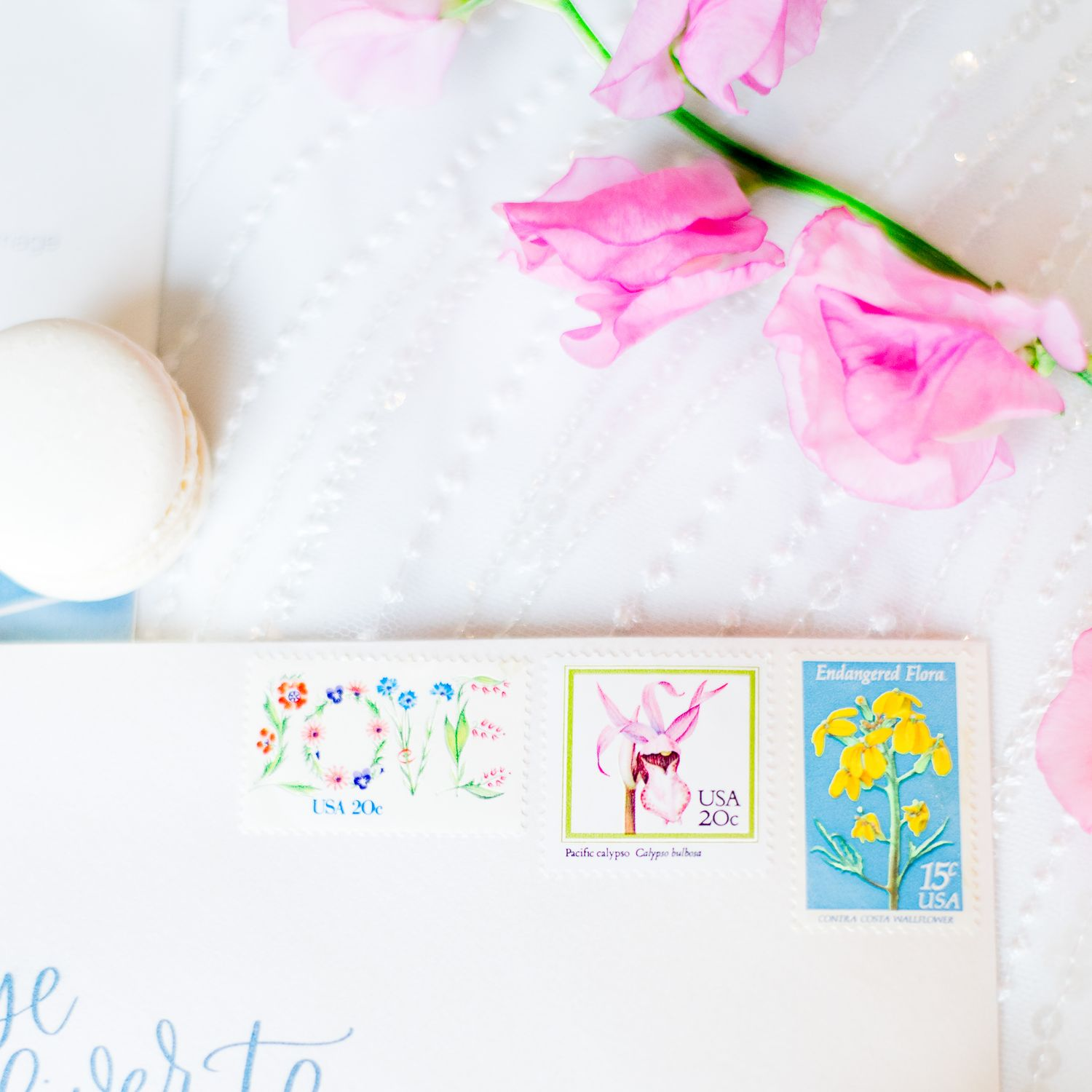 cute colorful floral stamps on envelope and sweet pea flower and macaron next to it