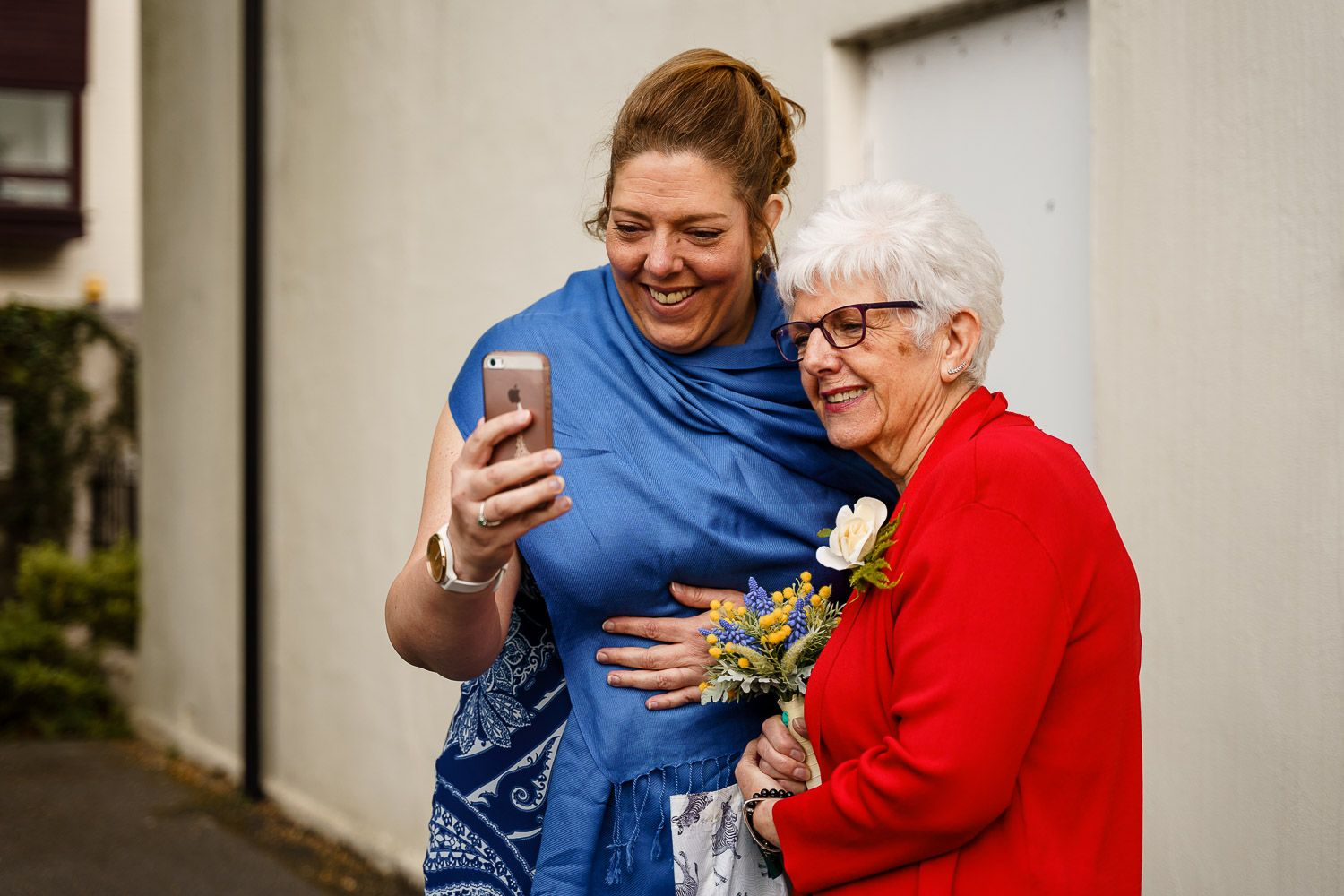 Bride and her mother speak to a relative in New Zealand via iphone on her wedding at Southampton Registry Office.