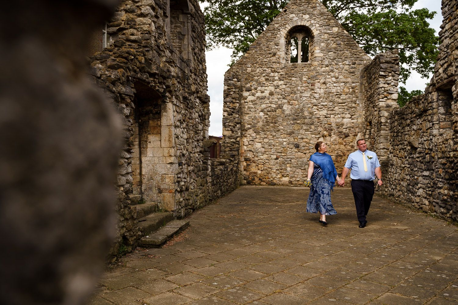 Bride and groom walk through medieval ruin in Southampton after their registry office wedding.