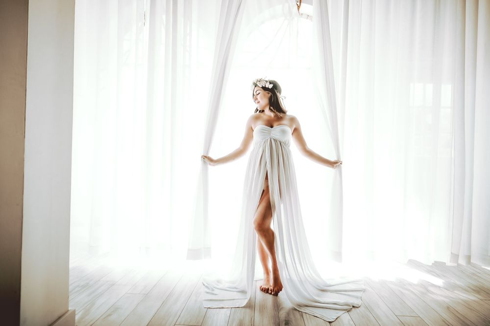 mother to be posing beautifully with pure white curtains during her maternity session at the studio of Roots & Memories