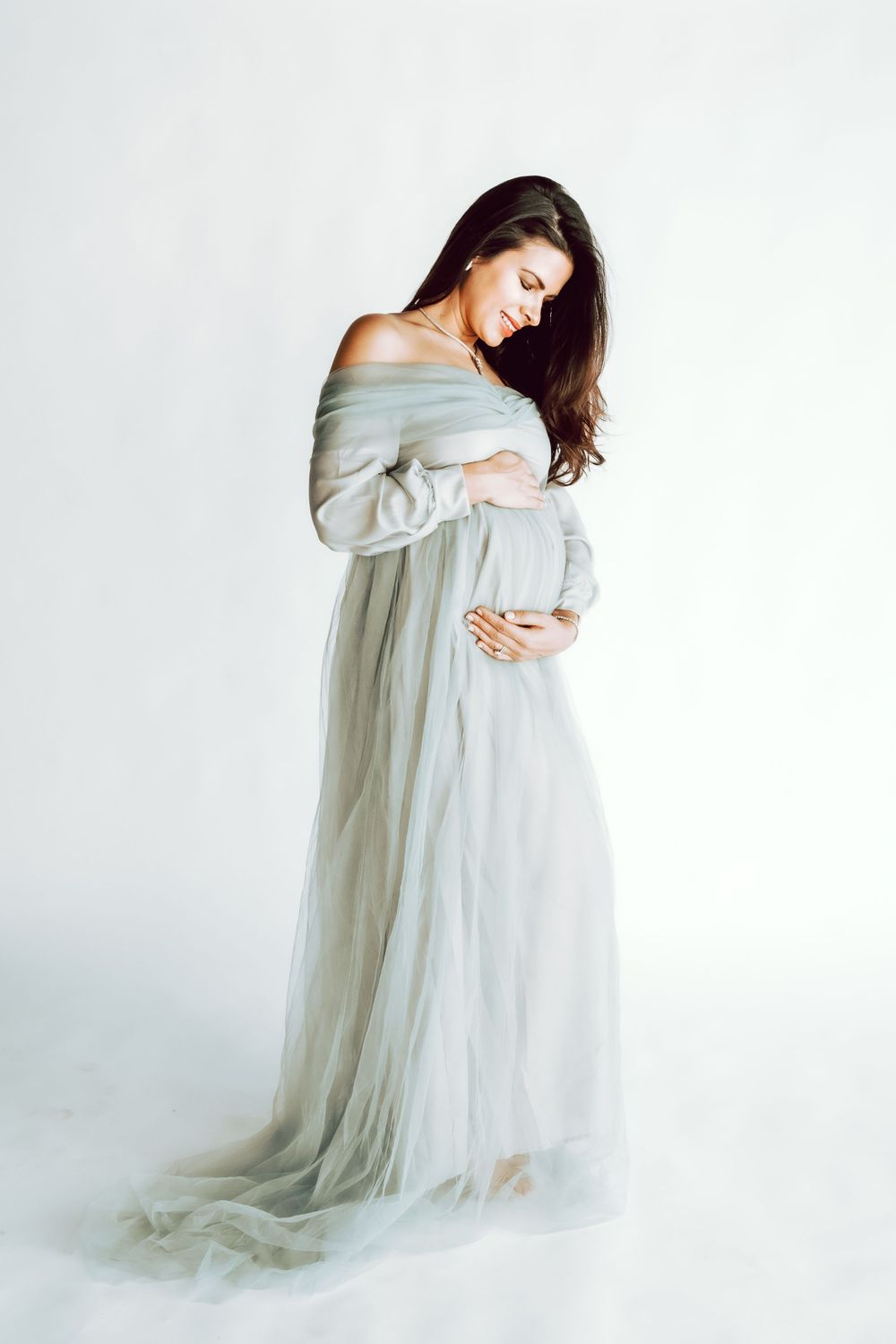 fabulous pregnant mom cradling her belly during her maternity session at a studio in Great Neck