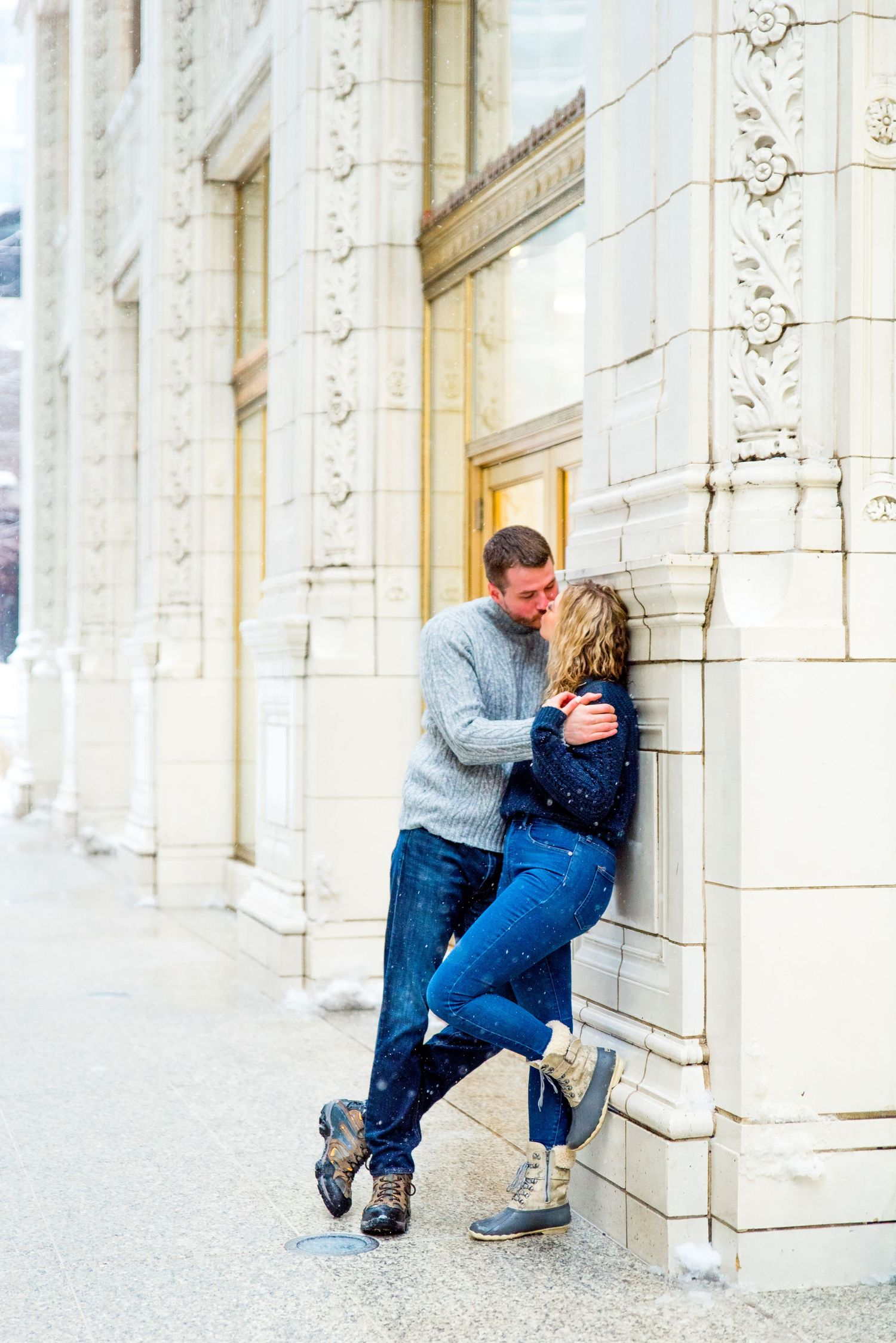 couple in grey and navy sweaters kissing against wall at Wrigley Building in the snow