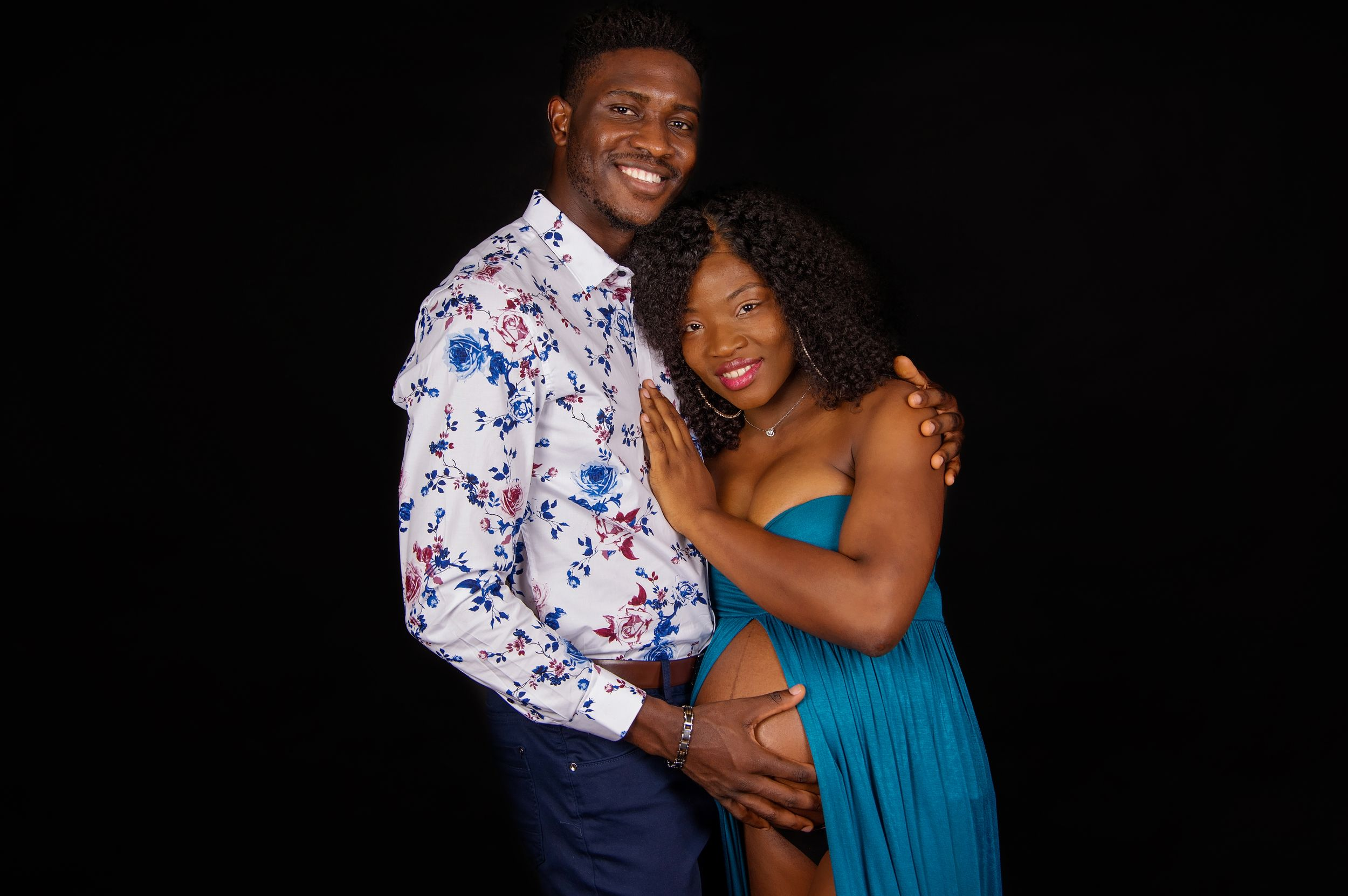 couple in studio posing and embracing pregnant belly